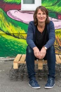 Stephanie Haury sitzt vor einer Graffiti-besprühten Wand