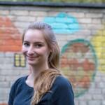 Redakteurin Mona vor einer bunt bemalten Wand