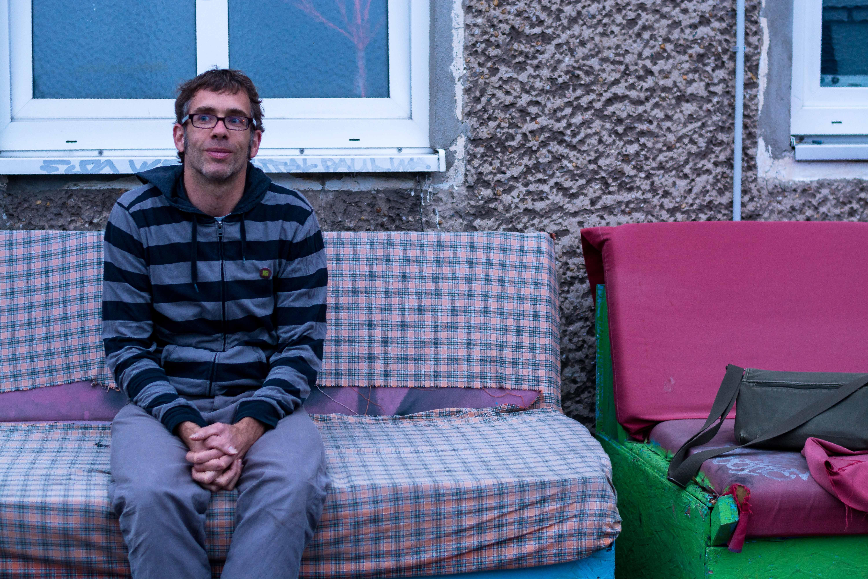 Sebastian Schlecht sitzt auf einer Bank mit blau-altrosa kariertem Stoffüberzug.
