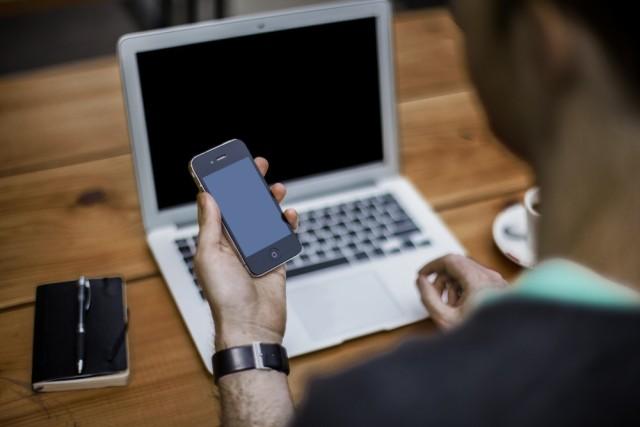 Ein Mann hält ein Smartphone an seinem Arbeitsplatz, neben seinem Laptop liegt ein Notizbuch.