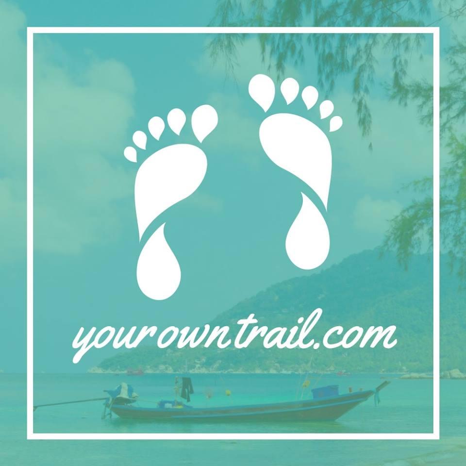 """Stilisierte nackte Füßen und der weiße Schriftzug """"yourowntrail.com"""" auf einem mit einer türkisfarbenen Folie überlagerten Foto eines kleinen Bootes."""
