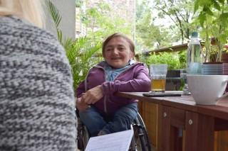 Rebecca Maskos sitzt in ihrem Rollstuhl am Balkontisch vor einem Glas Tee.
