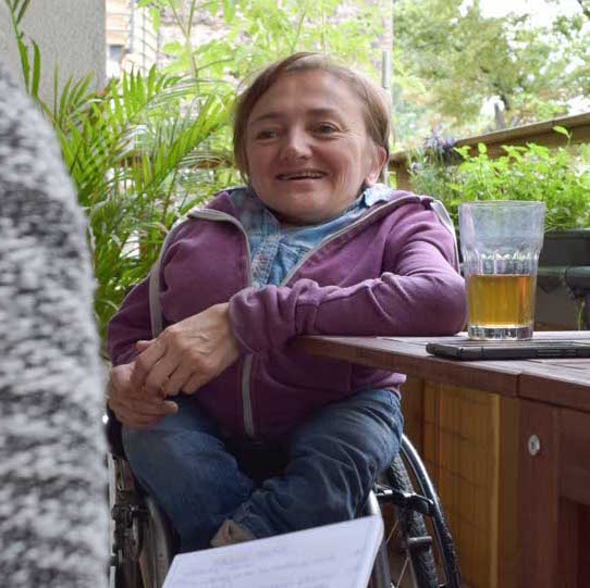 Rebecca Maskos sitzt mit einem Tee an ihrem Balkontisch
