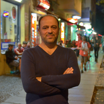 Yahya Al-Aous, 41 Jahre alt, steht freundlich lächelnd mit verschränkten Armen auf der Sonntagsstraße am Berliner Ostkreuz.