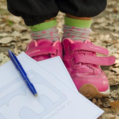 Ein Schreibblog mit Stift liegt an Kinderschuhen