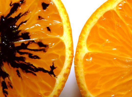 Es sind zwei Orangenhälften zu sehen, eine gute und eine schlechte.