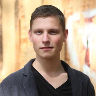 Redakteur Julian Kugoth vor einer Bretterwand