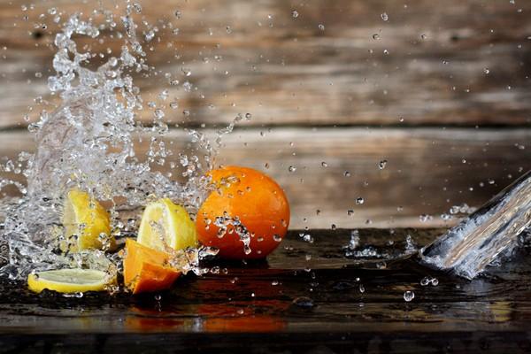 Um Zitronen und Orangen spritzt Wasser.