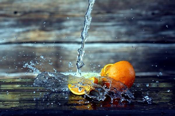 Ein Wasserstrahl spritzt auf eine aufgeschnittene Orange