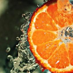 Eine Orangenscheibe umgeben von Wassertropfen