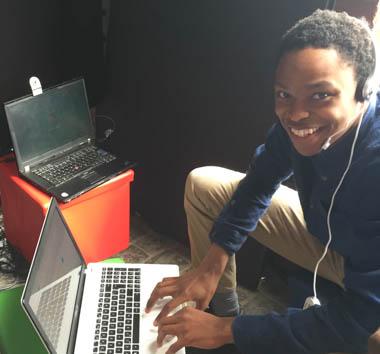 Junge mit Headset sitzt vor MacBook