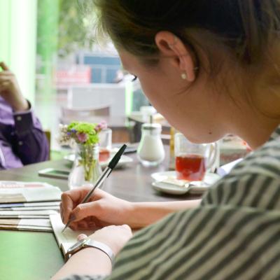 Eine weibliche Person schreibt in einem Café etwas in ein Notizbuch