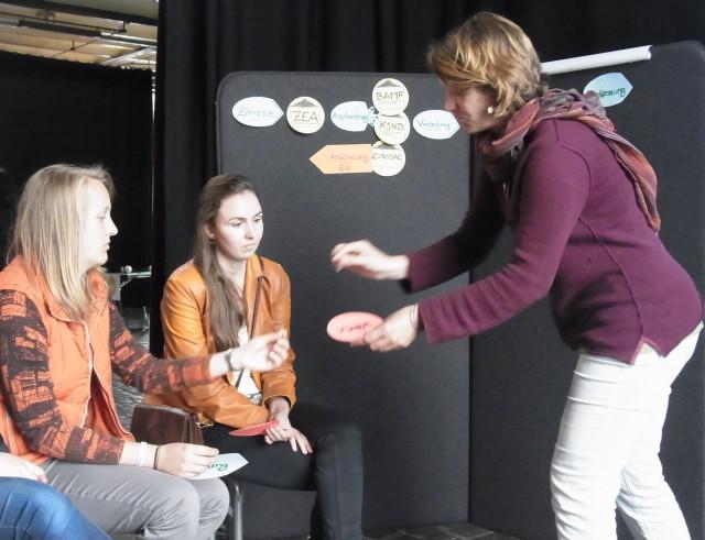 Zwei Teilnehmerinnen des Workshops sitzen vor der Wand, an der der Weg der Asylantragsstellung erarbeitet wird. Pia nimmt einer Teilnehmerin eine Karteikarte ab, um sie anzuheften.
