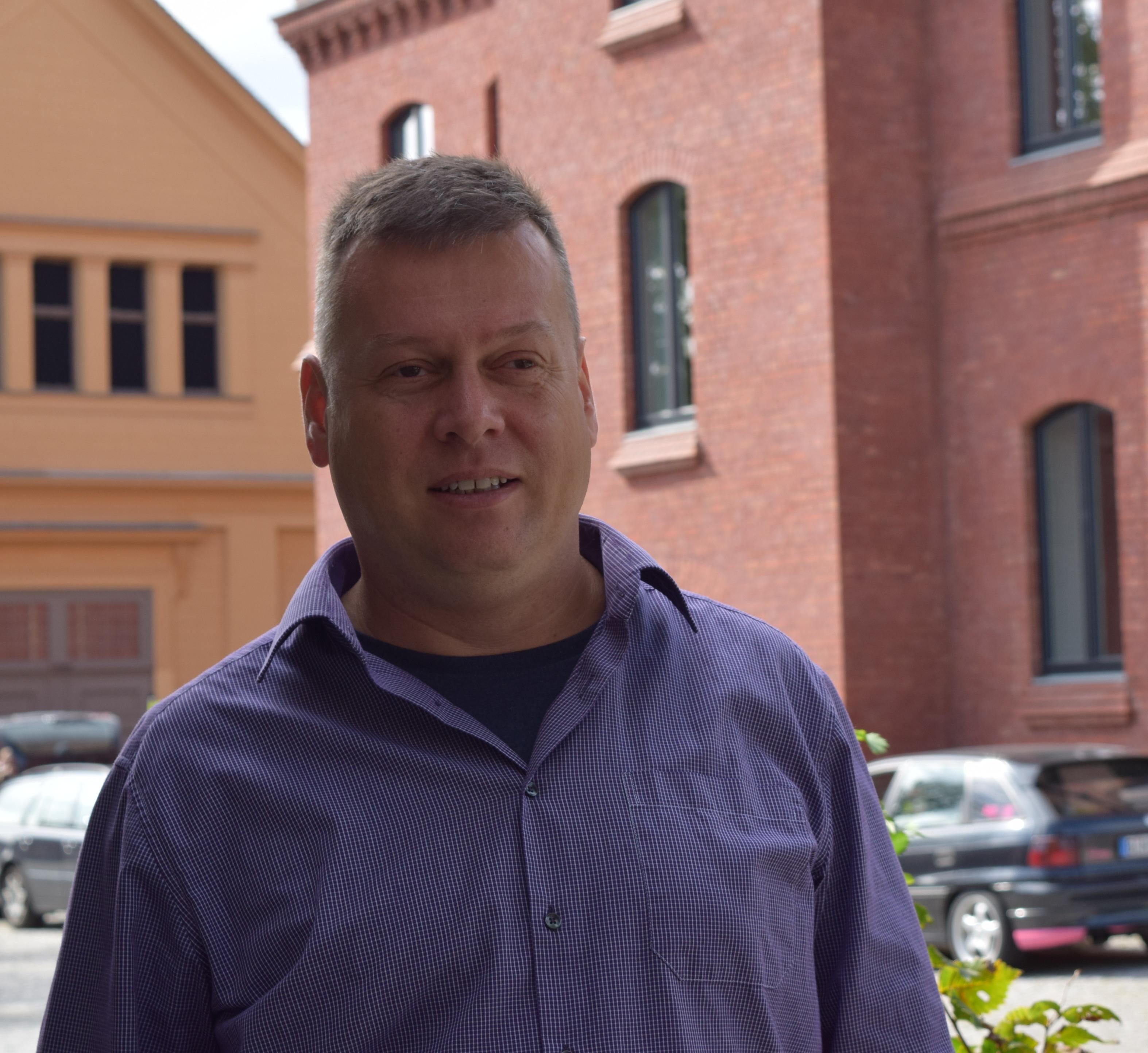 Stadtverordneter Uwe Fröhlich (Bündnis 90/ Die Grünen) steht vor einem roten Backsteingebäude und berichtet über Fairtrade-Towns. Foto: Lilith Grull