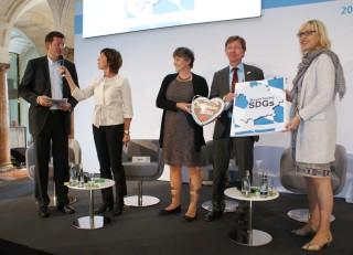 Die Bayrischen SDGs werden an Staatsministerin Merk übergeben. Foto: Annika Althoff