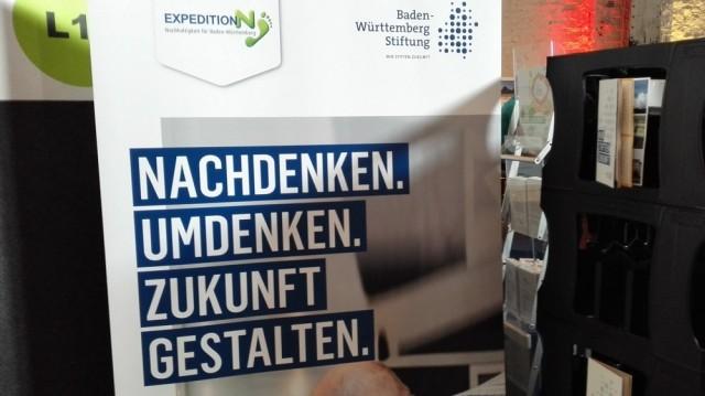 """Ein Banner der Baden-Würtemberg-Stifung. Darauf steht """"Nachdenken. Umdenken. Zukunft gestalten"""" in Großbuchstaben. Rechts finden sich einige Flyer und BÜcher"""