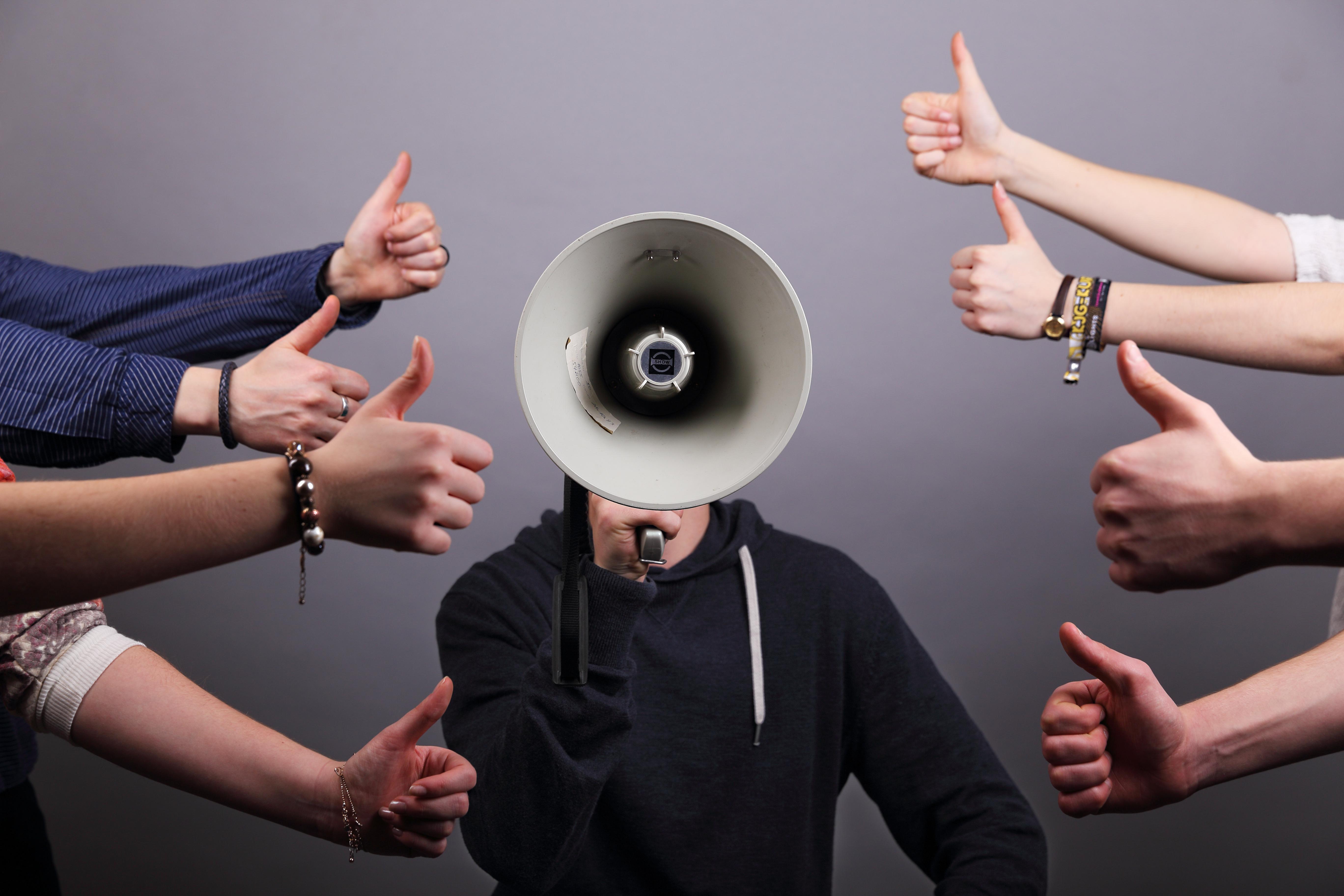 Einem Menschen mit Megaphon werden positive Daumen entgegen gestreckt