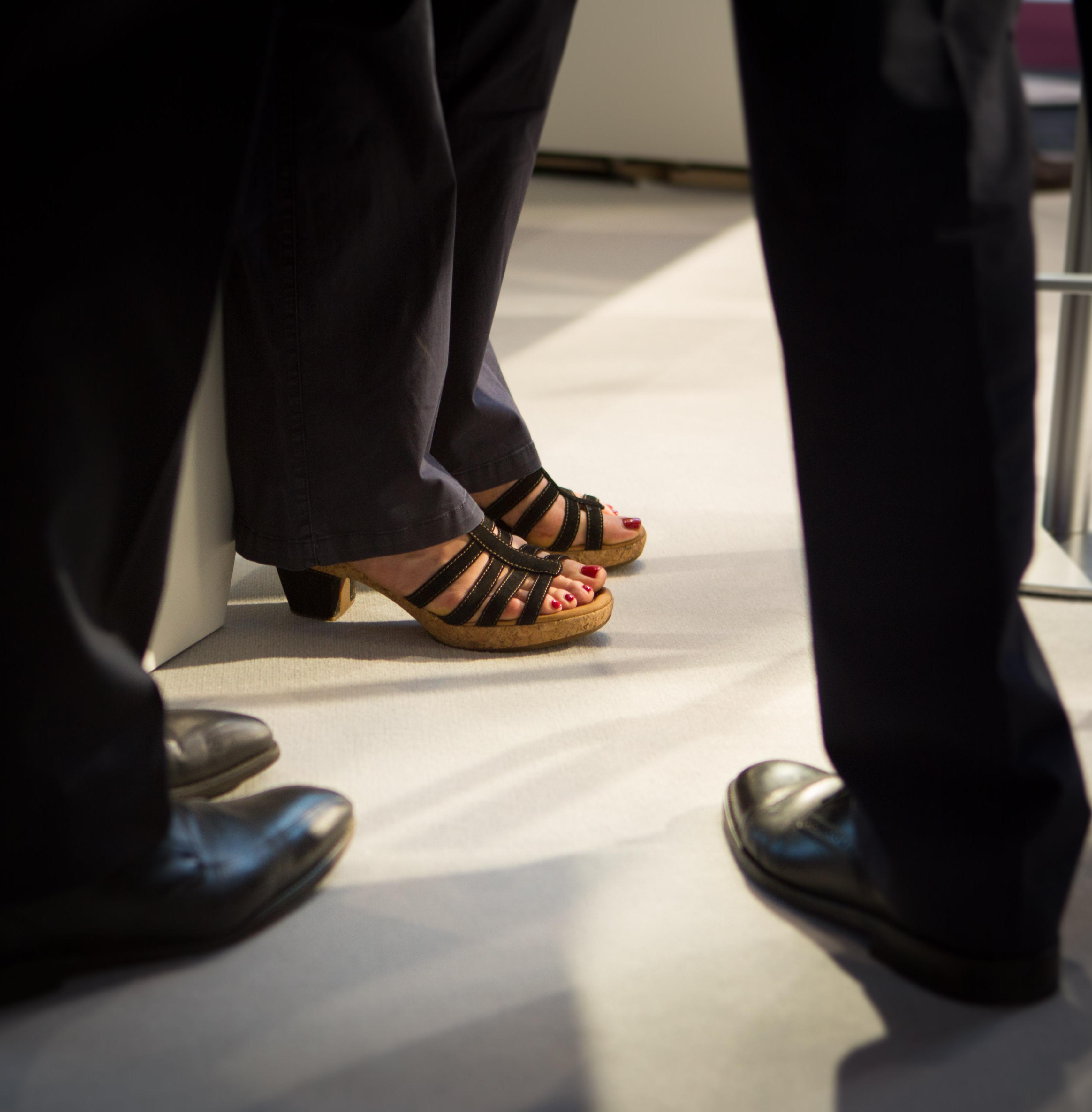Füße in weiblichen Schuhen zwischen Männerschuhen