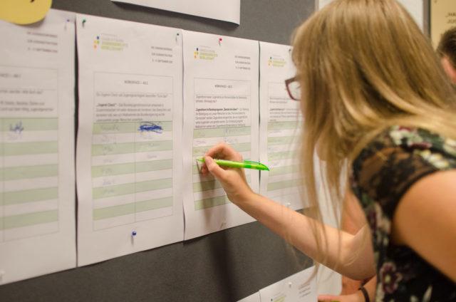 Eine Teilnehmerin sucht sich ihre Workshops für das Wochenende aus (Foto: Jonas Walzberg)
