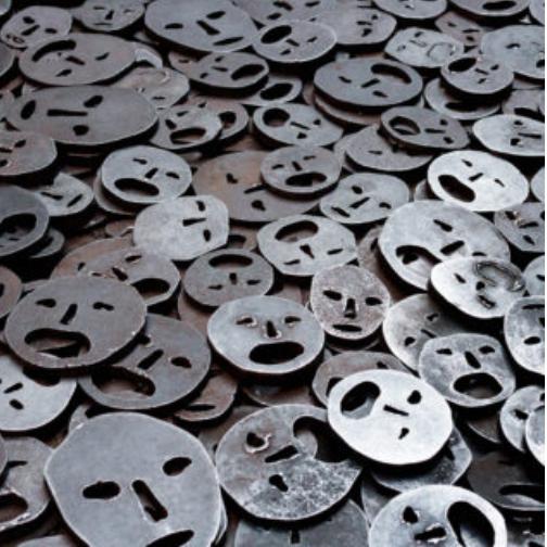 Eine Reihe von metallischen Gesichtern, 2 dimensional und entfremdet, wie Münzen auf dem Boden verteilt.