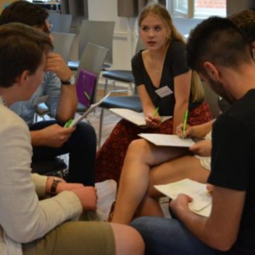 Eine kreative Runde auf der Jugenkonferenz. Vier Personen sitzen und bilden einen Kreis.