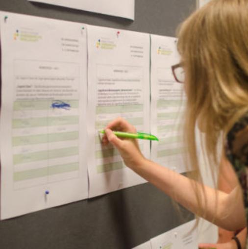 Eine Teilnehmerin sucht sich ihre Workshops für das Wochenende aus.