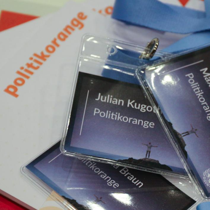politikorange-notizblag und Namensschilder der YouthCon 2016 für die Redakteure liegen auf einem Haufen. Foto: Charles Lothar