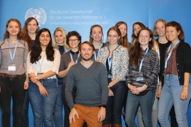 Das politikorange-Redaktionsteam zur YouthCon 2016 steht vor einem hellblauen Banner der Deutschen Gesellschaft für die Vereinten Nationen e.V.. Foto: Charles Lothar