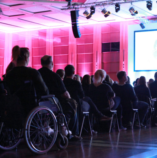 Bei der Auftaktveranstaltung des 16. Jugendhilfetags sitzt eine Rollstuhlfahrerin neben den anderen Teilnehmenden im Mittelgang mit Blick zur Bühne