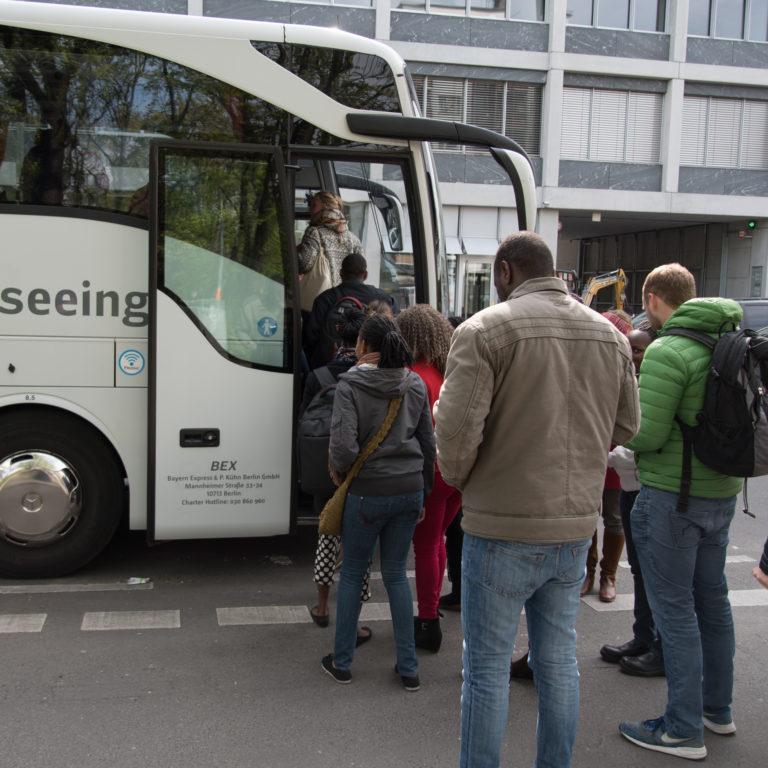 Menschen steigen in einen Reisebus. Foto: Jonas Walzberg