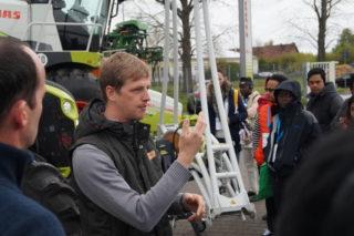 'CLAAS' Mitarbeiter Malzahn erklärt der internationalen Gruppe einen Mähdrescher