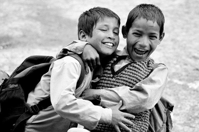 Zwei lachende Schulkinder, die sich umarmen