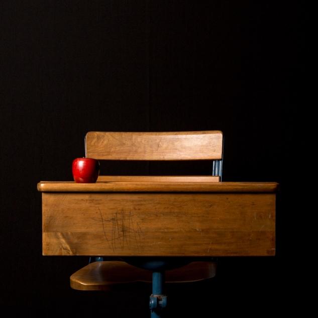 Eine hölzerne Schulbank vor schwarzem Hintergrund mit Apfel