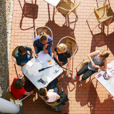 Pięć osób siedzących dookoła stołu – widok z góry