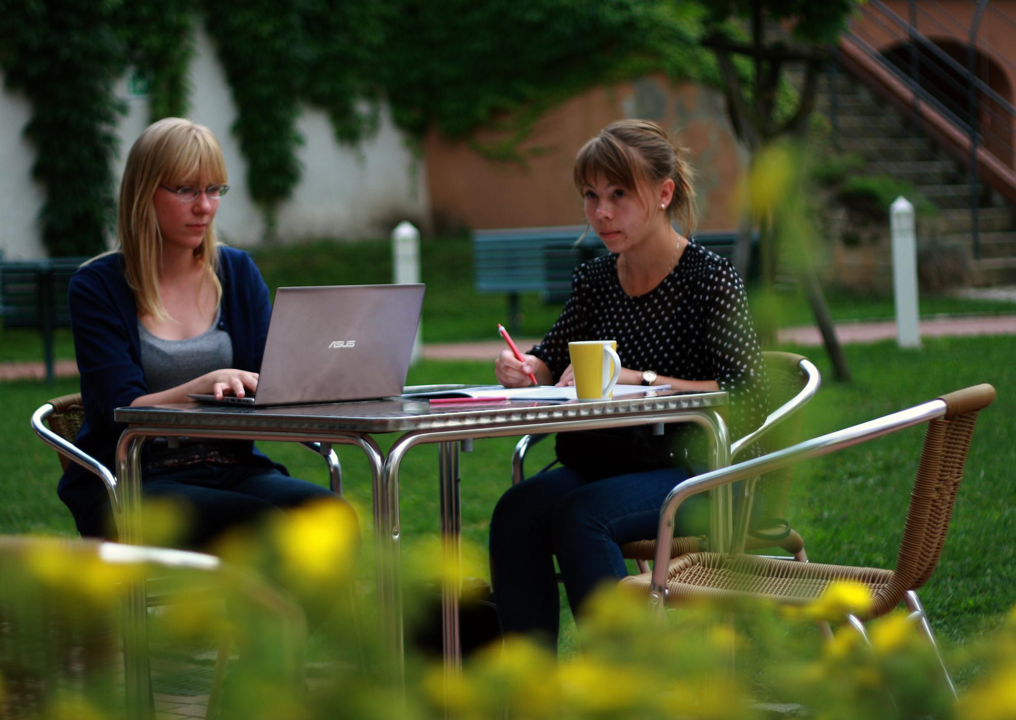 Dwie kobiety siedzą przy stole, jedna pracuje przy laptopie, druga robi notatki w zeszycie