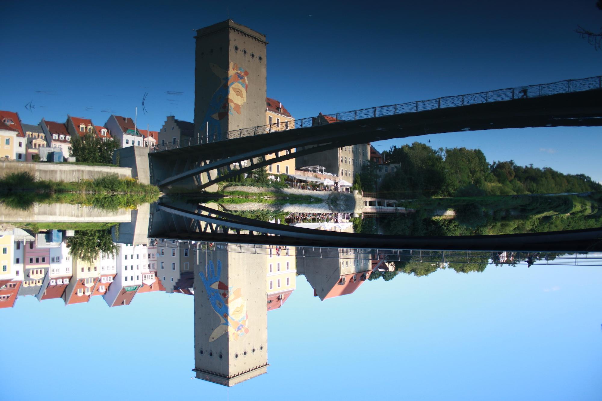 Bild eines Turms und Brücke hinter einem Fluss. Der Fluss spiegelt beides und erzeugt so eine Irritation beim Betrachter.