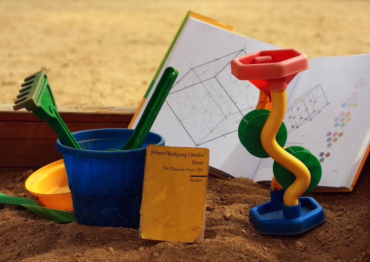 Ein Sandkasten, in dem neben Spielzeug auch aufgeschlagene Bücher und ein Schreibblock mit Stift liegen