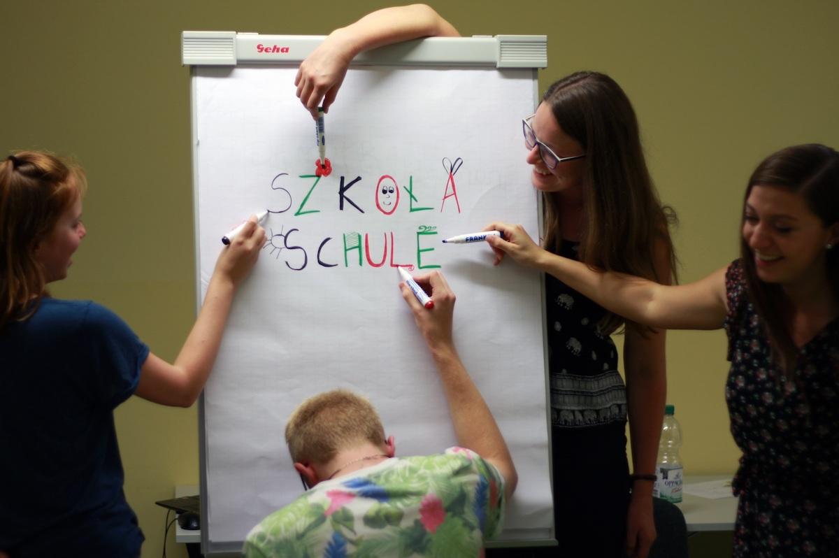 """Auf einem Blatt Papier steht """"Schule"""". Drei Hände verzieren das Wort."""