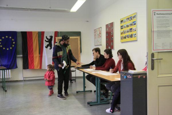 Mann gibt Stimmzettel im Wahllokal ab.