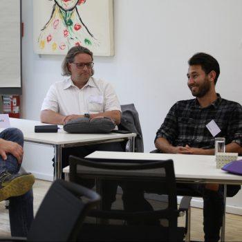 3 Männer im Seminarraum. Sie lächeln (größtenteils) während sie sich unterhalten.