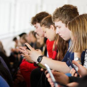 Junge Menschen sitzen gemeinsam da und schauen auf ihre Handys